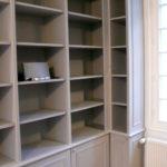 Bibliothèque avec corniche et portes avec moulures.