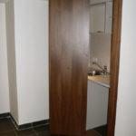 Kitchenette avec plan de travail en Corian. Porte pliante placage Noyer US satiné.